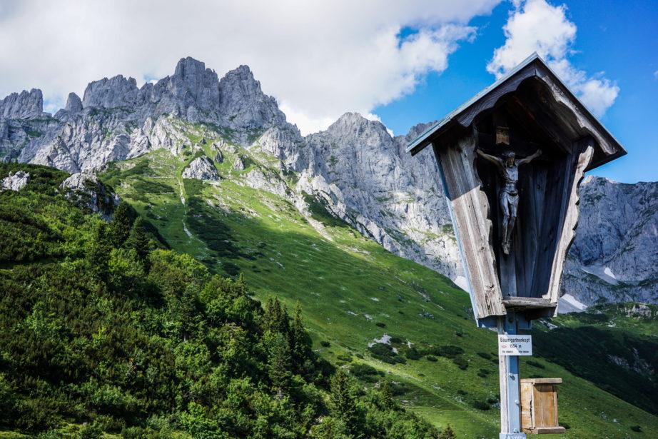 Das Gipfelkreuz vom Baumgartenköpfl vor einer prächtigen Bergkulisse.